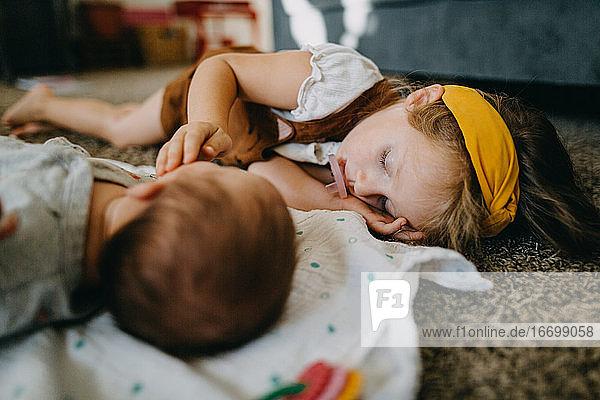 Preschool girl sleeping on floor with baby and sucking on a pacifier Preschool girl sleeping on floor with baby and sucking on a pacifier