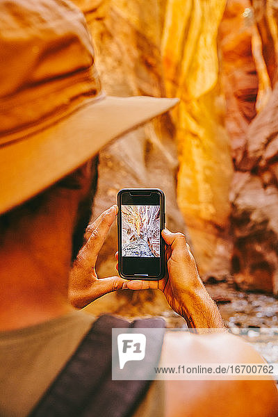 Young man wearing hat taking picture of slot canyons in Kanarra Falls
