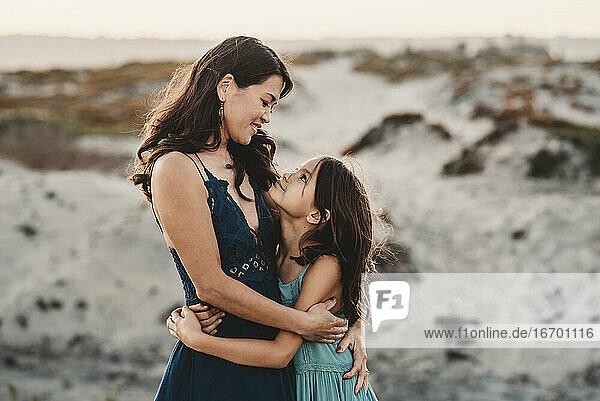 Glückliche Mutter  die ihre 8 Jahre alte Tochter am Strand umarmt