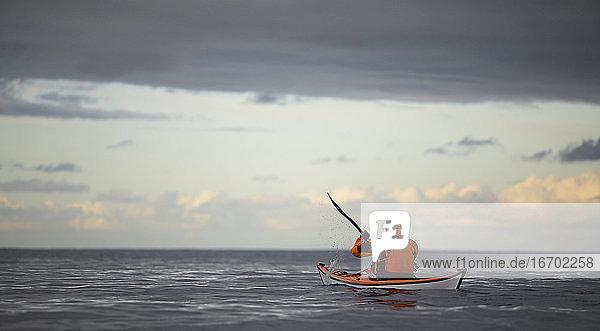 Reifer Mann steuert sein Seekajak durch die ruhigen Gewässer um Reykjavik Reifer Mann steuert sein Seekajak durch die ruhigen Gewässer um Reykjavik