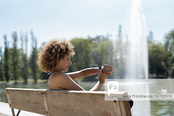 woman on a bench by the lake using her smartwatch