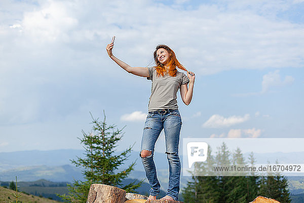 girl makes selfie on a smartphone against the background of the carpathian mountains