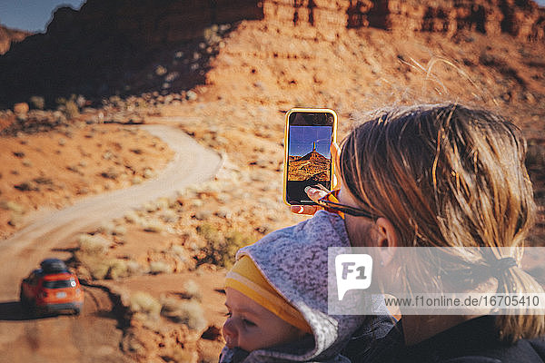 A woman with a child is taking pictures in Valley of the Gods  Utah