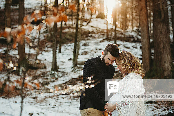 Couple with hands on pregnant belly outdoors in winter on a sunny day