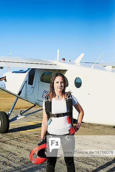 Young female skydiver with backpack in an airfield with plane