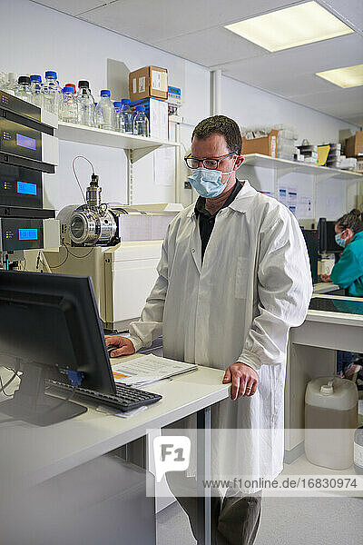Male scientist in face mask using computer in laboratory