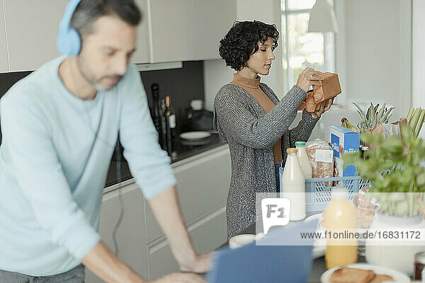 Couple working from home and unloading groceries in kitchen
