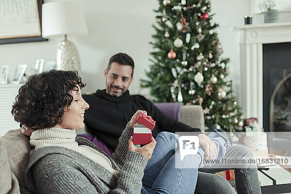 Wife opening Christmas gift from husband on living room sofa