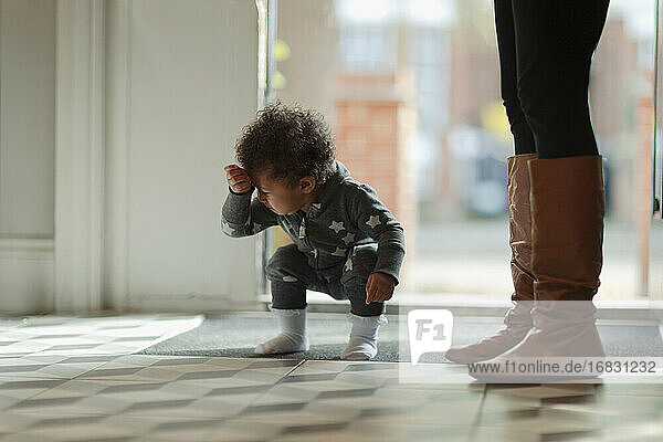 Cute baby girl in pajamas crouching at front door