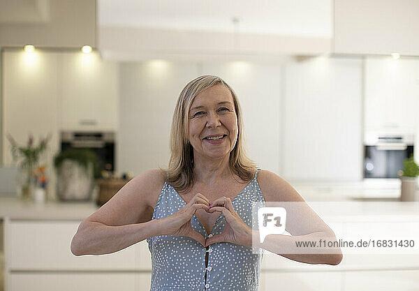 Portrait beautiful happy senior woman gesturing heart shape in kitchen