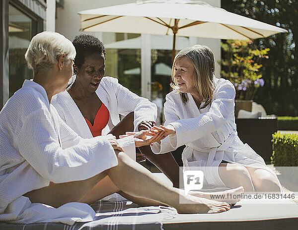 Senior women friends in spa bathrobes on sunny hotel patio