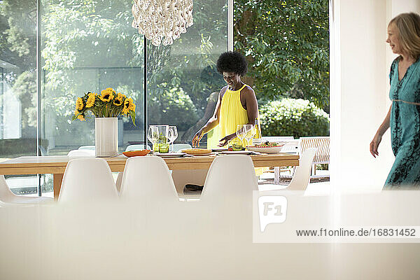 Mature woman in dress setting table for lunch in sunny dining room