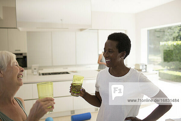 Happy senior women friends drinking water after exercising at home
