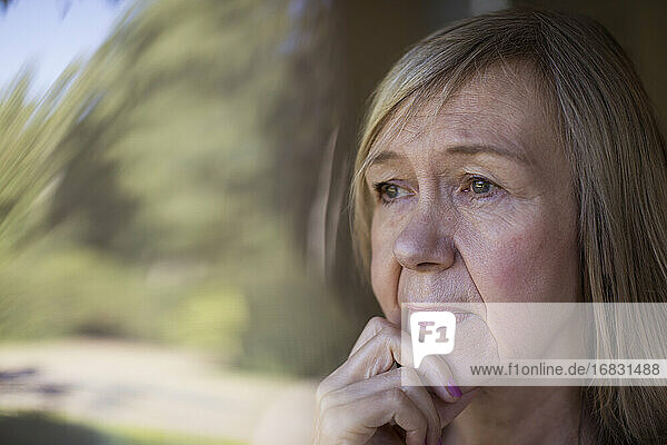 Close up worried senior woman looking out window