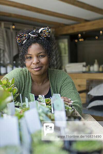 Portrait female shop owner at succulent display in plant nursery