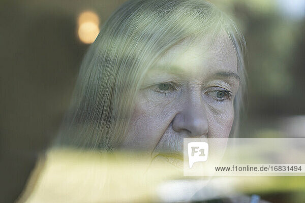 Close up worried senior woman at window