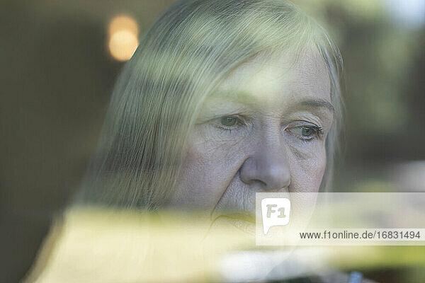 Close up worried senior woman at window