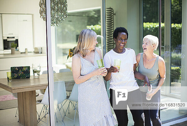 Happy senior women friends drinking and laughing on sunny patio