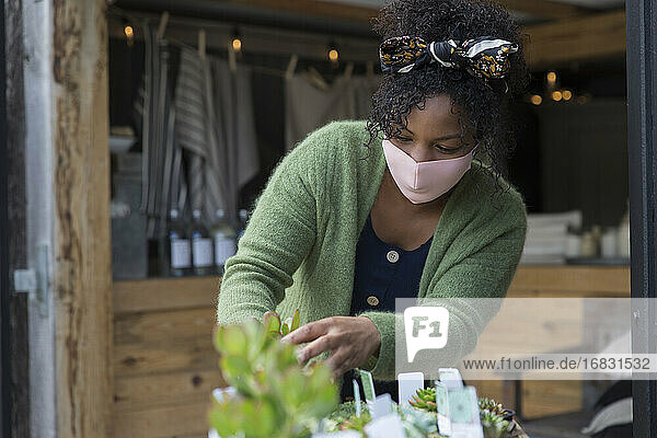 Female shop owner in face mask tending to succulent plants