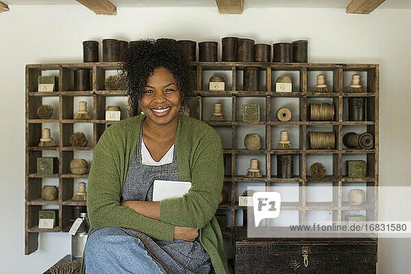 Portrait happy confident female shop owner at vintage display