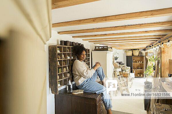 Portrait confident female shop owner at vintage display