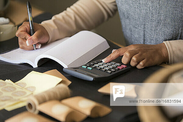 Close up shop owner with calculator filling in ledger