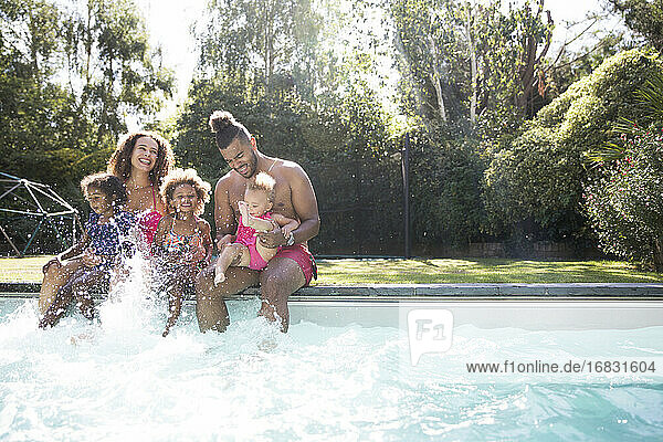 Playful family splashing in sunny summer swimming pool