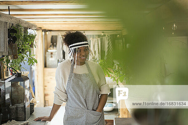 Woman in protective face shield working in plant nursery