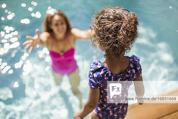 Daughter preparing to jump into arms of mother in sunny swimming pool