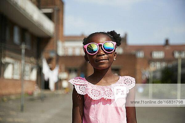 Portrait cute girl in bright pink sunglasses