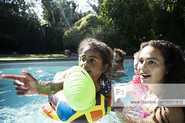Mother and daughter on inflatable raft playing in sunny swimming pool