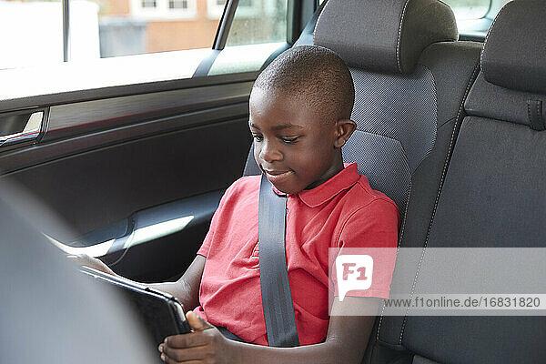 Boy using digital tablet in back seat of car