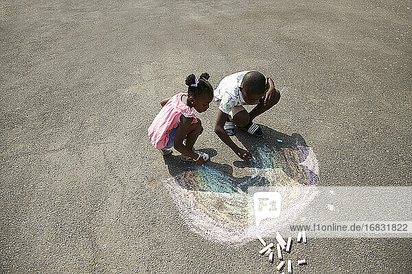 Brother and sister drawing rainbow with sidewalk chalk on pavement