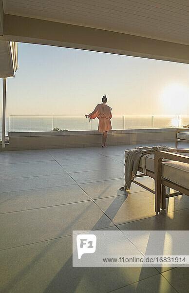 Woman in bathrobe enjoying ocean sunset view from luxury balcony