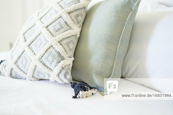Close up decorative pillow with tassel on bed