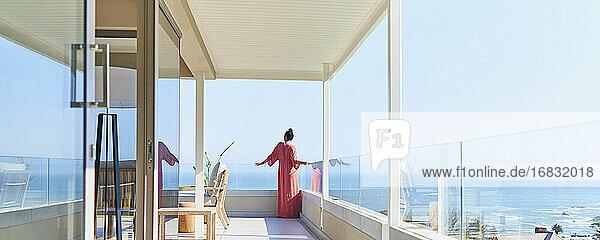 Woman in long dress enjoying sunny scenic ocean view on luxury balcony