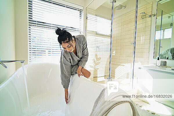 Woman in bathroom preparing soaking tub for bath in sunny bedroom