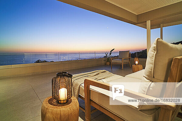 Lantern and armchair on luxury patio with scenic sunset ocean view