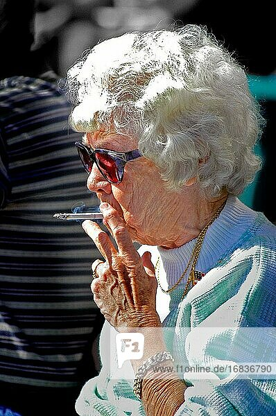 Old woman smoking a cigarette outside.