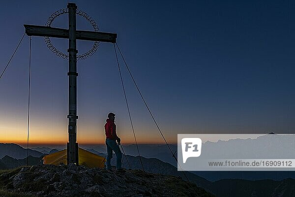 Sunrise over Ammergau mountains  in the foreground summit cross of the Geierkopf with mountaineer and tent  Reutte  Ammergau Alps  Tyrol  Austria  Europe