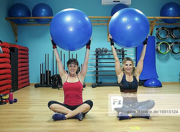 Two young women exercising in gym  using inflatable exercise ba