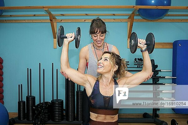 Two young women exercising in gym  doing weight workout