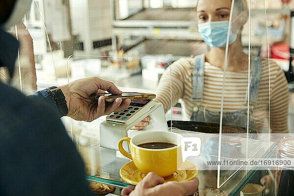 Frau mit Gesichtsmaske hinter dem Sicherheitsgitter eines Cafés  die dem Kunden ein kontaktloses Zahlungsterminal anbietet