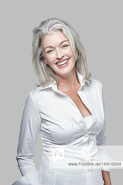 Portrait  attractive vivacious mature Caucasian woman with silver hair  laughing.