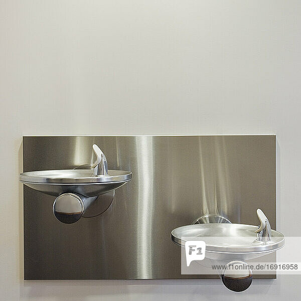 Two metal drinking fountains mounted on wall at different heights.