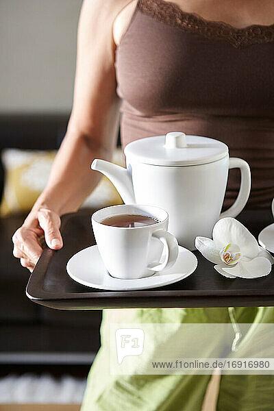Frau trägt eine Porzellan-Teekanne und Tasse auf einem Tablett