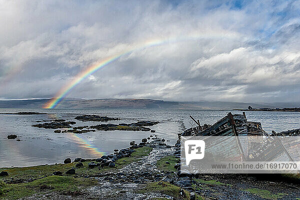 Rainbow and beached old wooden fishing boats on shore at Salen