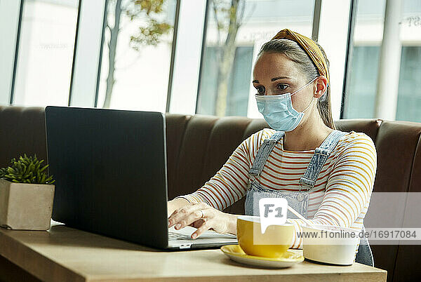 Woman wearing a face mask seated in a cafe using a laptop