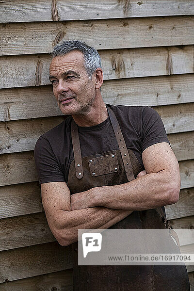 Portrait of male barista with short grey hair  leaning against wooden wall.