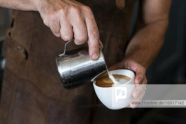 Nahaufnahme eines Barista mit brauner Schürze  der Cappuccino einschenkt.